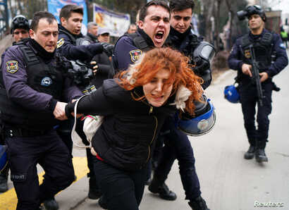 Riot police detain a demonstrator during a protest against the dismissal of academics from universities following a post-coup emergency decree, outside the Cebeci campus in Ankara, Turkey, Feb. 10, 2017.