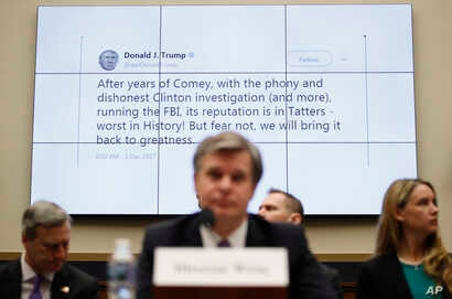 FILE - A tweet by President Donald Trump is displayed behind FBI Director Christopher Wray as he testifies during a House Judiciary hearing on Capitol Hill in Washington, Dec. 7, 2017, on oversight of the Federal Bureau of Investigation.