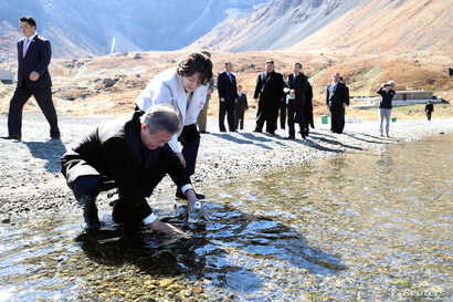 South Korean President Moon Jae-in with his wife, first lady Kim Jung-sook, standing next to him, fills a plastic bottle with water from the Heaven Lake of Mt. Paektu, North Korea, Sept. 20, 2018.