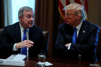 FILE - U.S. President Donald Trump listens to U.S. Senator Dick Durbin, D-Ill., during a meeting with legislators on immigration reform at the White House in Washington, Jan. 9, 2018.  In a follow-up meeting January 11, Trump questioned why the Unite...