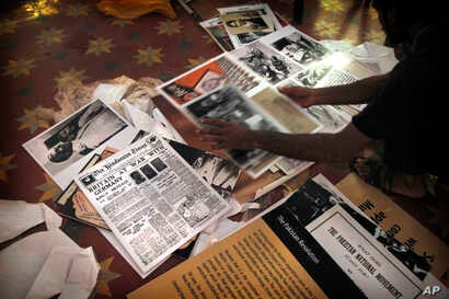 A worker sorts through photographs, newspaper clippings, and other material, Aug. 12, 2017, that will cover the walls at the Partition Museum, set to open in Amritsar, India, 32 kilometers (20 miles) from the border with Pakistan.
