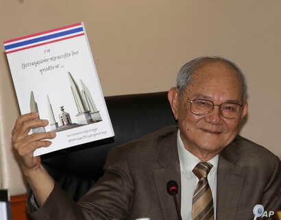 Chairman of the Constitution Drafting Commission Meechai Ruchupan holds the draft of new constitution during a press conference at the Parliament in Bangkok, Thailand, March 29, 2016.