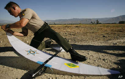 FILE - A Los Angeles County Sheriff's Deputy assembles an autonomous drone aircraft used by the military and law enforcement, during a demonstration June 16, 2006, in Redlands, Calif.