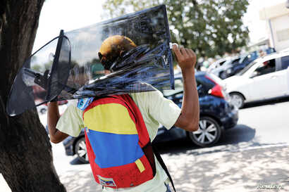 A Venezuelan man wears a backpack with the colours of Venezuelan flag as he sells car accessories at traffic lights in Boa Vista, Brazil, Nov. 18, 2017.