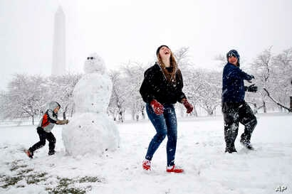 Dane Lariscy, 5, left, works on a snowman as his siblings, Amanda, 17, and Blaze, 15, laugh while having a snowball fight on the National Mall during the Florida family's first snowfall, March 21, 2018, in Washington.