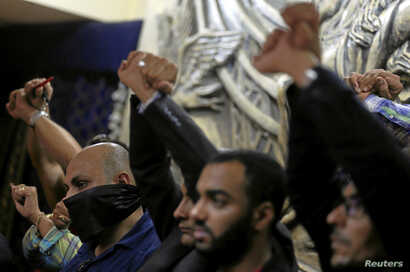 Journalists gesture in protest against the arrests of fellow journalists during a news conference on World Press Freedom Day at the Egyptian press syndicate's headquarters in downtown Cairo, Egypt, May 3, 2016.