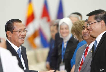 Cambodian Prime Minister Hun Sen, left, smiles as he greets international observers for the July 29 general election, during a welcome meeting at Peace Palace, in Phnom Penh, Cambodia, July 28, 2018.