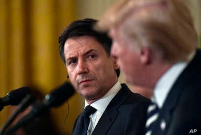 Italian Prime Minister Giuseppe Conte, left, listens as President Donald Trump, right, speaks during a news conference in the East Room of the White House in Washington, July 30, 2018.
