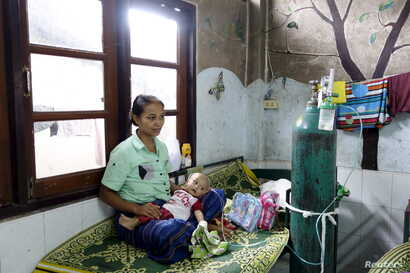 FILE - A refugee from Myanmar sits with her sick child at the Mae Tao clinic in the bordering town of Mae Sot, Oct. 30, 2015. Myanmar's landmark election triggers migrants' mixed emotions - hope that a hated government will be defeated, and fear of t...