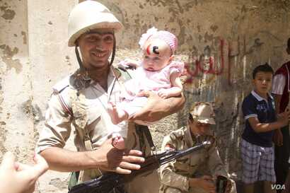 """An Egyptian soldier poses with a baby with the letters """"CC""""  on her forehead standing for president Sissi in front of one of the polling stations in Bashteel in Giza, Egypt. Sissi has enjoyed support from Egypt's army, long regarded as a pillar of st..."""