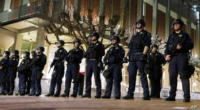 FILE - In this Feb. 1, 2017, photo, University of California, Berkeley police guard the building where Breitbart News editor Milo Yiannopoulos was to speak in Berkeley.
