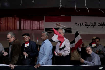 Egyptian men wave national flags as they wait in line to vote during the first day of the presidential election in front of a polling site in Cairo, Egypt, Monday, March 26, 2018.