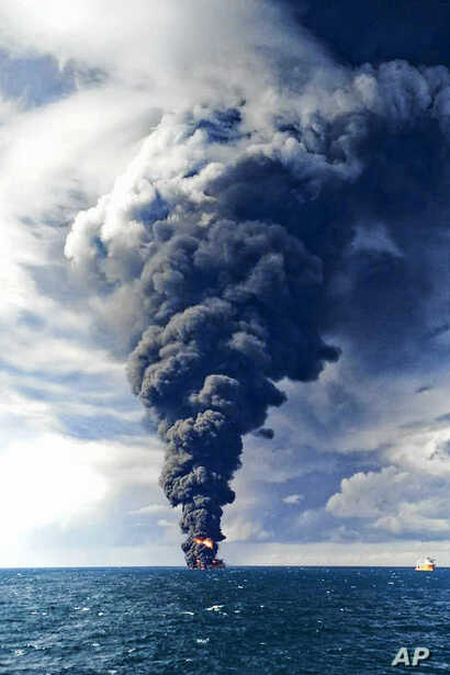 In this photo provided by China's Ministry of Transport, smoke and flames rise from the burning Iranian oil tanker Sanchi in the East China Sea off the eastern coast of China, Jan. 14, 2018.