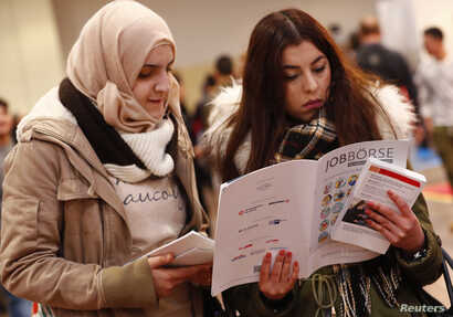 Two women visit the second job fair for migrants and refugees in Berlin, Germany, Jan. 25, 2017.