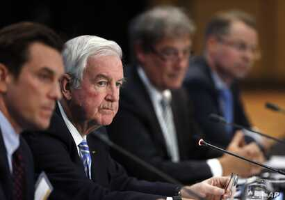 FILE - Craig Reedie, second from left, president of the World Anti-Doping Agency, (WADA), listens to a question during a news conference following a meeting in which WADA leadership voted to declare Russia's anti-doping operation out of compliance, i