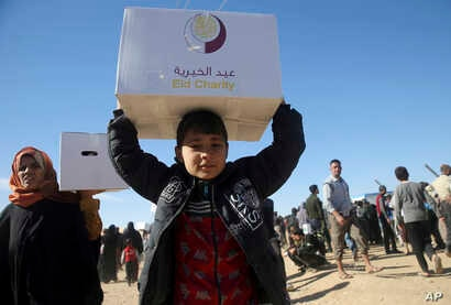 Iraqi citizens who fled the fighting between Islamic State militants and the Iraqi forces, carry boxes of aid supplies, at a camp for internally displaced people, in Khazer, east of Mosul, Iraq, Nov. 21, 2016.