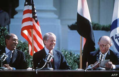 Egyptian President Anwar al-Sadat, left,  and US President Jimmy Carter laugh during Israeli Premier Menachem Begin' speech, before signing the Israel-Egypt Peace Agreement on March 26, 1979 on the north lawn of the White House, Washington DC. In 197...