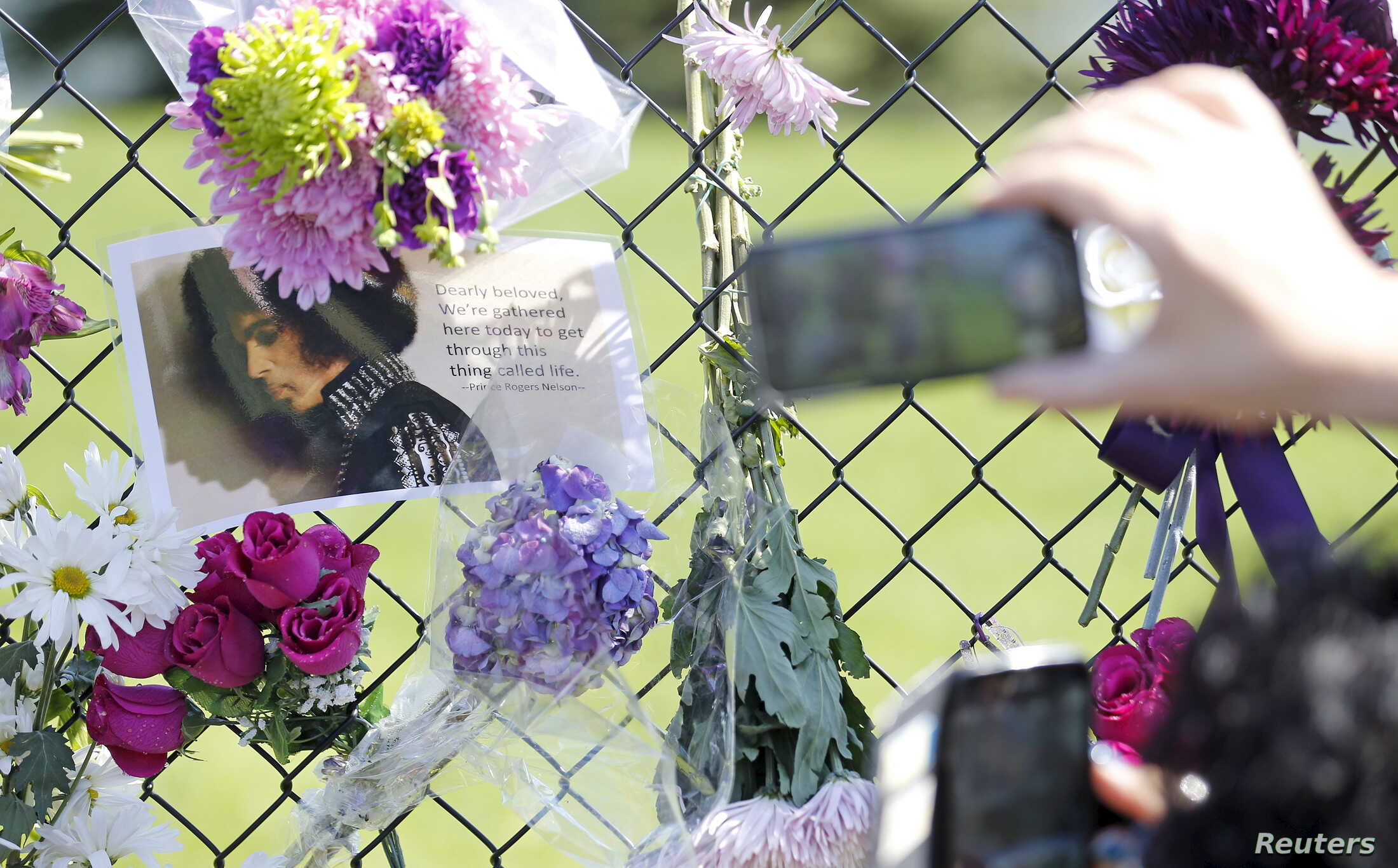Fans take pictures of a makeshift memorial to musician Prince outside the fence of Paisley Park, his home and recording studio in Chanhassen, Minnesota, a day after his death on Apr 22, 2016. (Reuters)