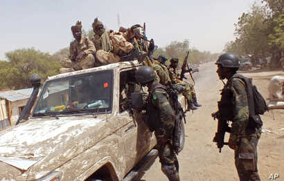 In this photo taken Feb. 19, 2015, Cameroon soldiers check a truck on the border between Cameroon and Nigeria as they combat regional Islamic extremists force's including Boko Haram.