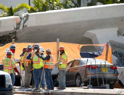 Workers wait near a section of a collapsed pedestrian bridge, March 16, 2018, near Florida International University in the Miami area. The pedestrian bridge, which was under construction, collapsed onto a busy Miami highway Thursday, crushing vehicle...
