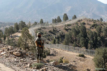 FILE - A soldier stands guard along the border fence at the Angoor Adda outpost on the border with Afghanistan in South Waziristan, Pakistan, Oct. 18, 2017.