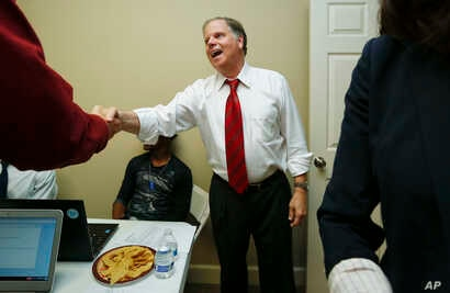FILE - Democratic Alabama U.S. Senate candidate Doug Jones stops along the campaign trial to greet volunteers, in Montgomery, Alabama, Nov. 29, 2017.