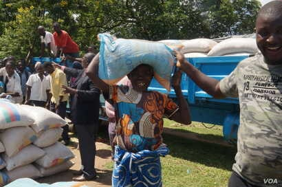 Marita Shati smiles after receiving a bag of maize from Abida Mia's Reach Out and Touch charity in Malawi.