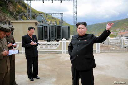 North Korean leader Kim Jong Un (R) gives field guidance during a visit to the construction site of the Paektusan Hero Youth Power Station near completion in this undated photo released by North Korea's Korean Central News Agency (KCNA) in Pyongyang,