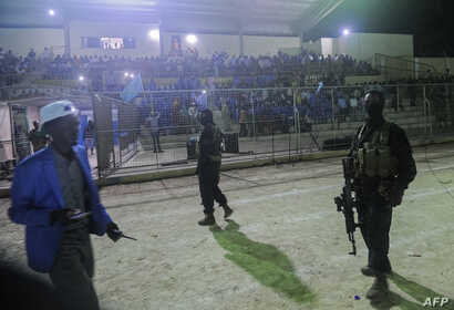 Somali security forces patrol during the soccer match between the Hodan (in orange) and Waberi districts — the first night game in 30 years at Konis Stadium, renovated by FIFA, in Modadishu, Somalia, Sept. 8, 2017.