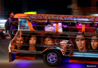 Commuters hang on to the back of a crowded jeepney in Cainta, Rizal, Philippines, Feb. 1, 2019.