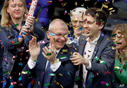 Green Party's gay rights activist Volker Beck (center) and fellow faction members celebrate with a confetti popper after German Federal Parliament, Bundestag, voted to legalize same-sex marriage in Berlin, Germany, June 30, 2017.