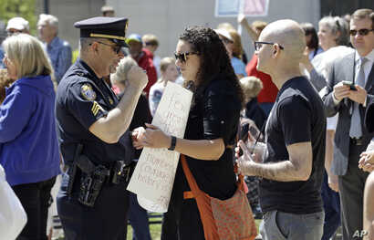 A police officer confronts a woman holding a sign at the North Carolina State Capitol in Raleigh, N.C., April 11, 2016.