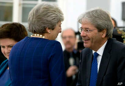 British Prime Minister Theresa May, left, speaks with Italian Prime Minister Paolo Gentiloni during an informal dinner ahead of an EU Digital Summit in Tallinn, Estonia, Sept. 28, 2017.