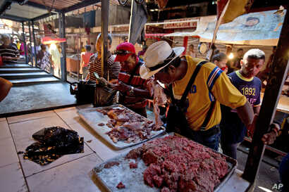 A customer smells a piece of spoiled meat at a market in Maracaibo, Venezuela, Aug. 19, 2018. Venezuelans are lining up at one of the country's largest markets to buy spoiled meat. At bargain prices, it's the only way they can afford beef.