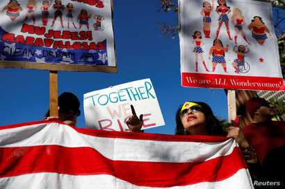 People hold an American flag during the second annual Women's March in Los Angeles, California, Jan. 20, 2018.