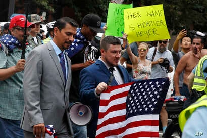 "White nationalist Jason Kessler, center, walks to the White House to rally on the one year anniversary of the Charlottesville ""Unite the Right"" rally, Sunday, Aug. 12, 2018, in Washington."
