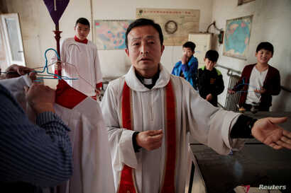 Father Ju Ruibin of the government-sanctioned Catholic church prepares for the procession on Palm Sunday in Youtong village, Hebei province, China, March 25, 2018.