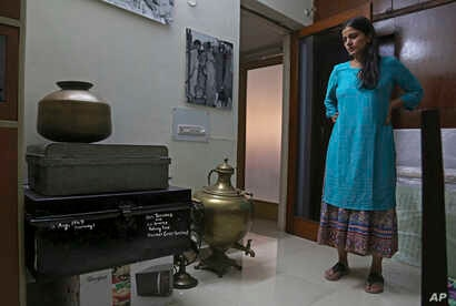 The CEO of India's new partition museum, Mallika Ahluwalia, looks at a steel trunk, which was among items donated by the relative of a person who had migrated to India during partition in 1947, in New Delhi, India, July 22, 2017.