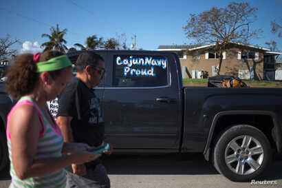 FILE - Volunteers with the Cajun Navy walk in the aftermath of Hurricane Irma on Chokoloskee Island, Florida, U.S. Sept. 12, 2017.