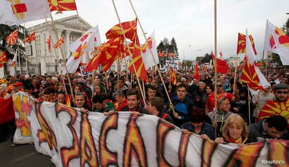 People protest marching through a street in Skopje, Macedonia, on April 3, 2017.