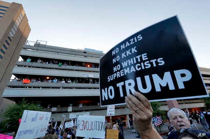 People protest outside the Phoenix Convention Center, Aug. 22, 2017, in Phoenix. Protests were held against President Trump as he hosted a rally inside the convention center.