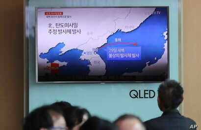 People sit in front of the TV screen showing a news program reporting about North Korea's missile firing, at Seoul Train Station in Seoul, South Korea, May 29, 2017.