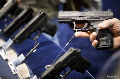 FILE - A Walther handgun is displayed at the Smith & Wesson booth at the Safari Club International Convention in Reno, Nevada, Jan. 29, 2011.