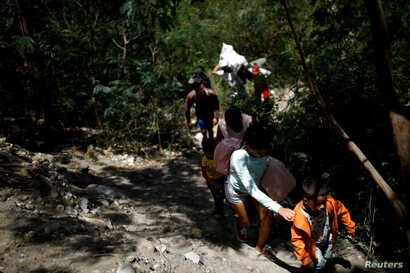 FILE - Migrants walk along a pathway after crossing illegally into Colombia across the Tachira river in Villa del Rosario, Colombia, Aug. 24, 2018.