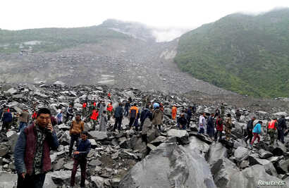 People search for survivors at the site of a landslide that destroyed some 40 households, where more than 100 people are feared to be buried in Xinmo Village, Sichuan Province, China, June 24, 2017.