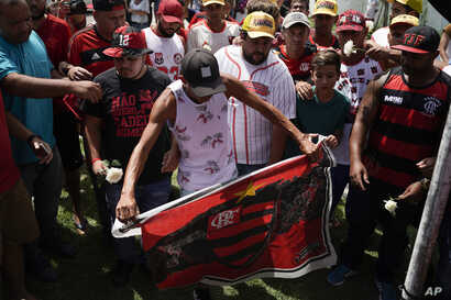 A fan holds a Flamengo flag as he and other fans pay homage to the fire victims at the entrance of the Flamengo soccer club training complex in Rio de Janeiro, Brazil, Feb. 8, 2019.