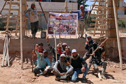 "Members of ""You Destroy and We Rebuild Brigade"" pose at a construction site in front of their banner depicting a still from their parody video that circulated on Syrian social media, in the rebel-held town of Saida, in Deraa province, Syria, May 24,..."