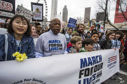 FILE - U.S. Rep. John Lewis leads a march of thousands through the streets of Atlanta, March 24, 2018. Participants in Atlanta and across the nation rallied against gun violence and in support of stricter gun control.