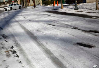 Ice covers a street as a car struggles to climb a hill in Atlanta, Jan. 17, 2018. The South awoke on Wednesday to a two-part Arctic mess. First came a thin blanket of snow and ice, and then came the below-zero wind chills and record-breaking low temp...