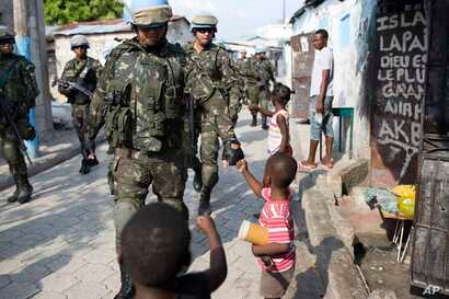 U.N. peacekeepers from Brazil bump fists with children as they patrol in the Cite Soleil slum, in Port-au-Prince, Haiti, Feb. 22, 2017. U.N. forces have patrolled since a 2004 rebellion engulfed the Caribbean country in violence.